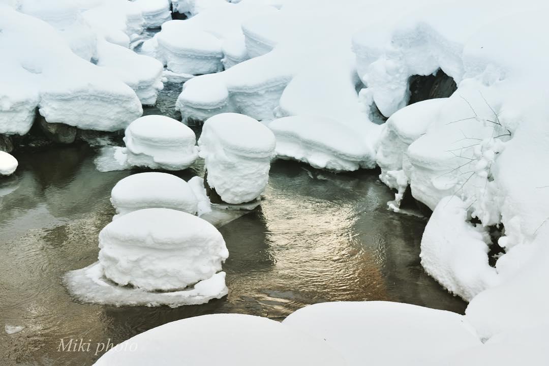 川の岩に積もる雪