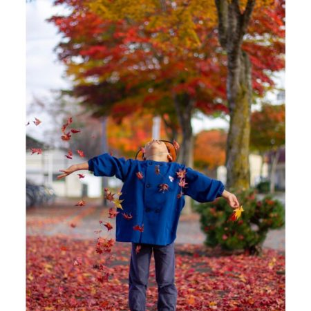 Boy enjoying autumn leaves